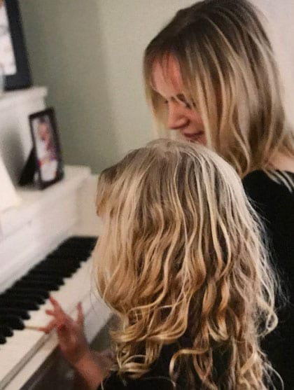 mother and daughter sitting at the piano