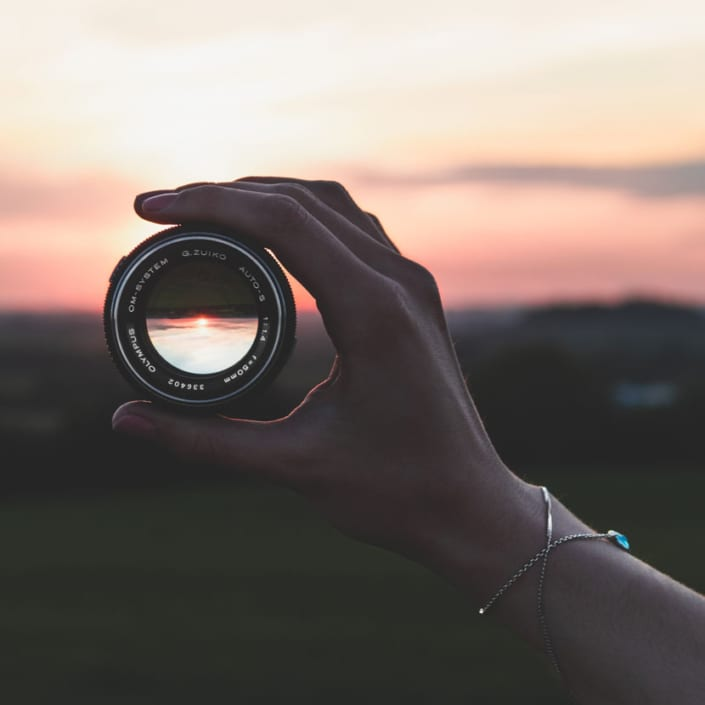 women lens in hand looking out at horizon