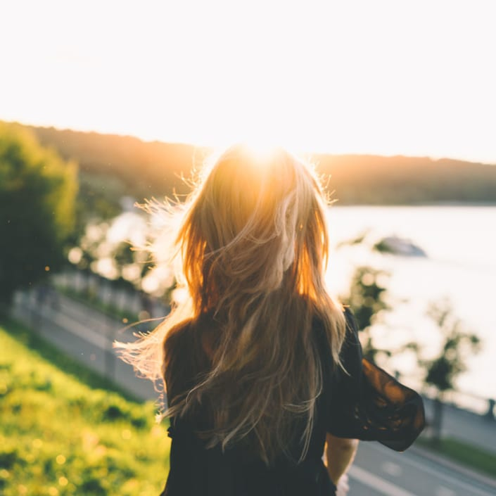woman in sunlight looking out at water