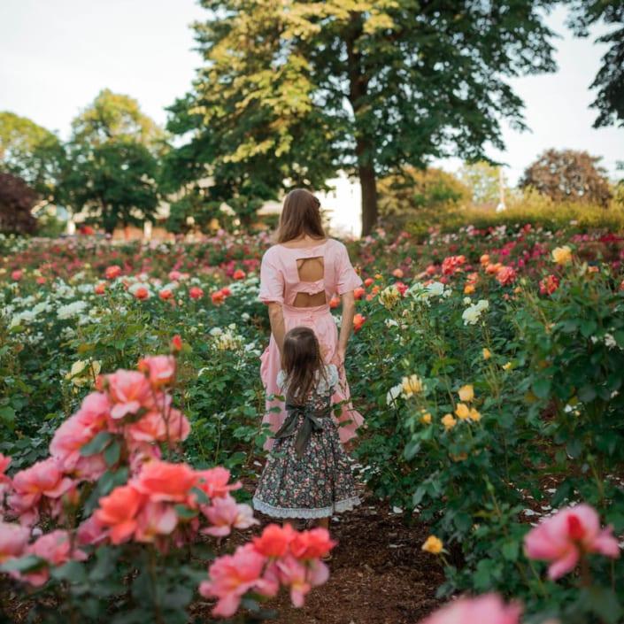mother leading child through garden