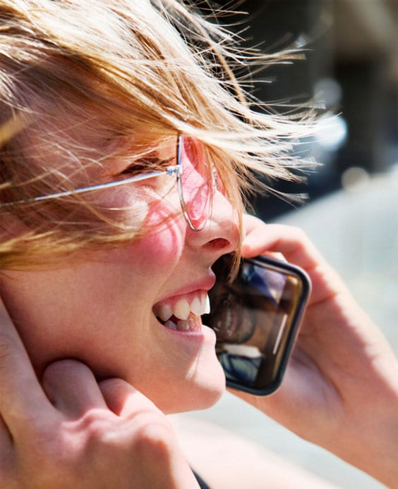 woman with rose colored glasses smiling on phone