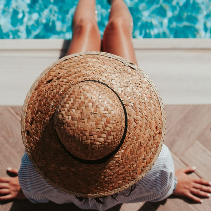 woman in straw hat at edge of pool