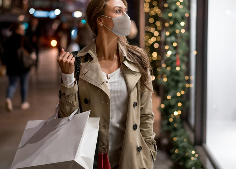 show woman looking into store window with mask on