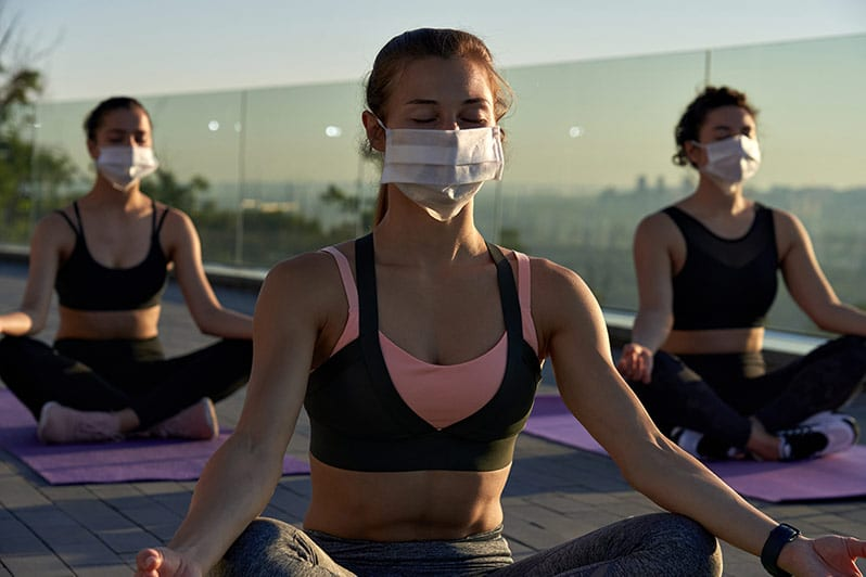 women wearing a mask and connecting with friends doing yoga