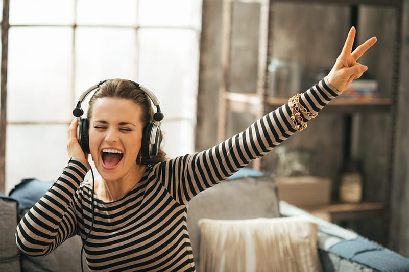 Woman listening to music and dancing away the winter blues