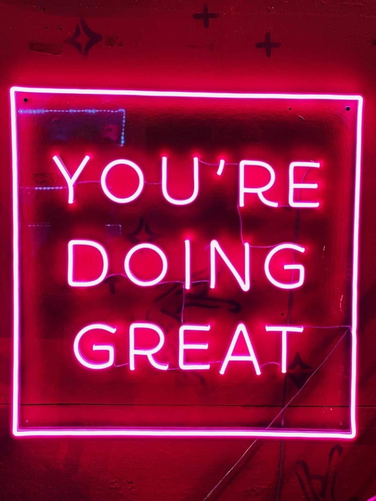 """pink neon sign that says """"you're doing great"""""""