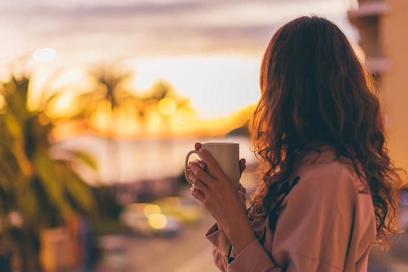 Woman taking a moment with coffee in the morning; a moment of self-care and self-compassion