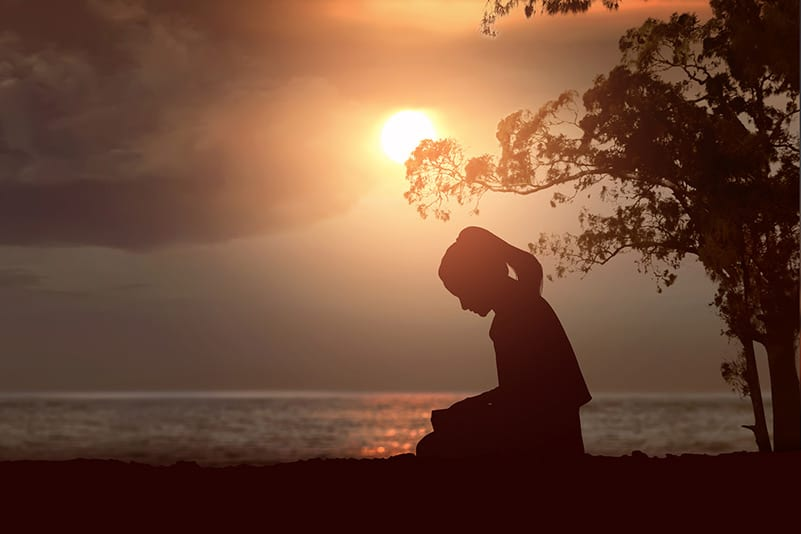 woman sitting in reflection during sunset - demonstrated solitude and self-compassion