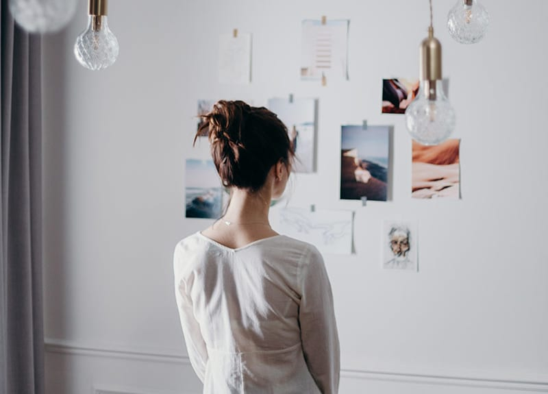 woman looking at images - getting inspired for vision board