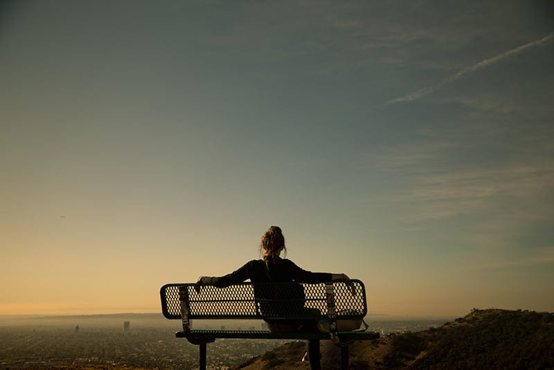 woman sitting alone on bench