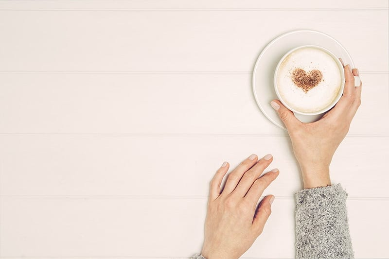 women holding a coffee cup with a heart