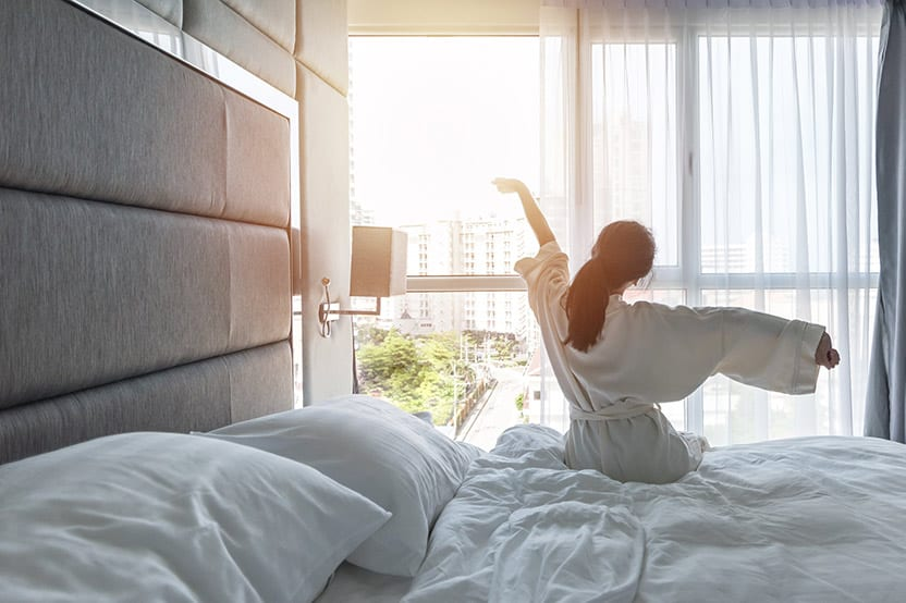 woman happily waking up to sunshine