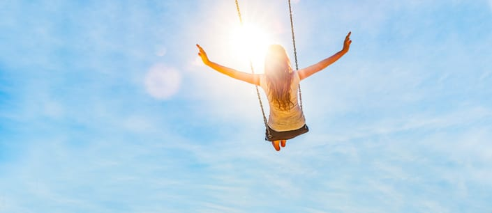 woman so happy swinging in sunshine