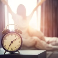 morning routine - alarm clock and woman getting out of bed