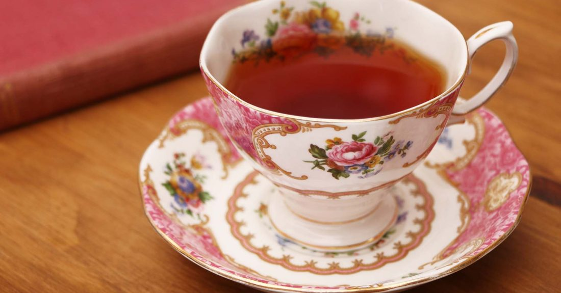 rose colored tea cup with book